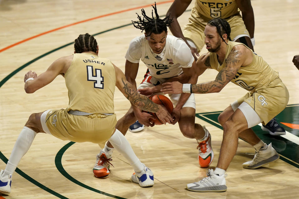 Georgia Tech guard Jordan Usher (4) and guard Jose Alvarado, right, defend against Miami guard Isaiah Wong during the first half of an NCAA college basketball game, Saturday, Feb. 20, 2021, in Coral Gables, Fla. (AP Photo/Lynne Sladky)