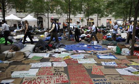 Morning commuters walk past Occupy Wall Street campaign protesters sleeping in Zuccotti Park, near Wall Street in New York in this September 27, 2011 file photo. As Occupy's two-year anniversary approaches on September 17, the movement that once captivated national attention has largely faded. REUTERS/Brendan McDermid/Files