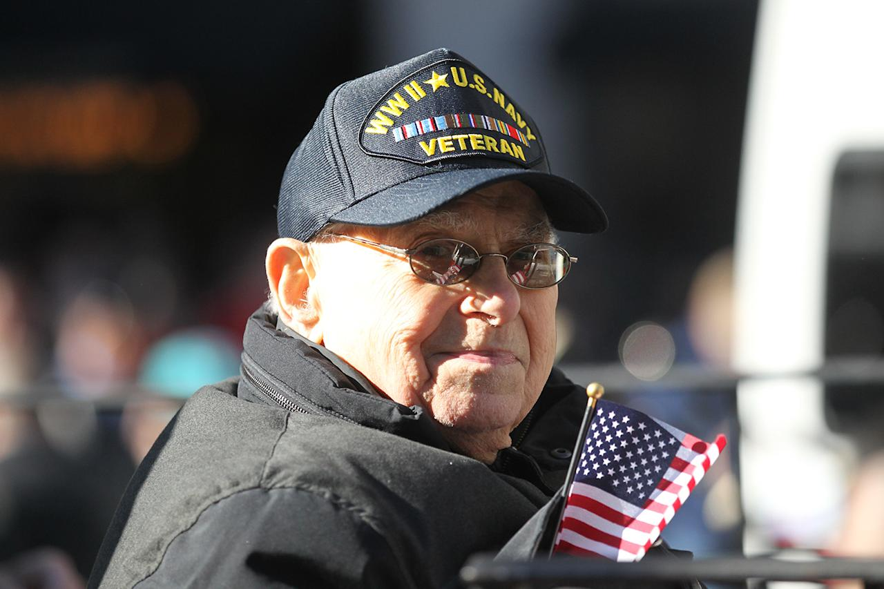 <p>A veteran smiles, waving a flag, on board a float moving up Fifth Avenue during the Veterans Day parade in New York City on Nov. 11, 2018. (Photo: Gordon Donovan/Yahoo News) </p>