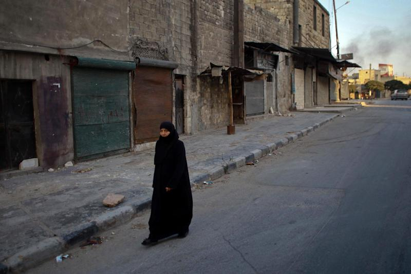 A Syrian woman walks on a street following a reported air strike by government forces on July 19, 2014 in the northern city of Aleppo (AFP Photo/Ahmed Deeb)