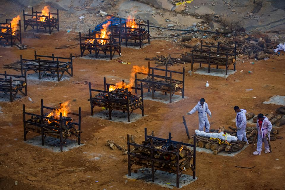 Men wearing PPE perform the last rites of a deceased relative in a disused granite quarry repurposed to cremate the Covid dead in Bengaluru, India. Source: Getty