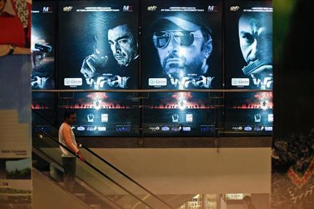 "A man rides an escalator past posters of the movie ""Waar"" at the Atrium cinemas in Karachi October 23, 2013. REUTERS/Akhtar Soomro"