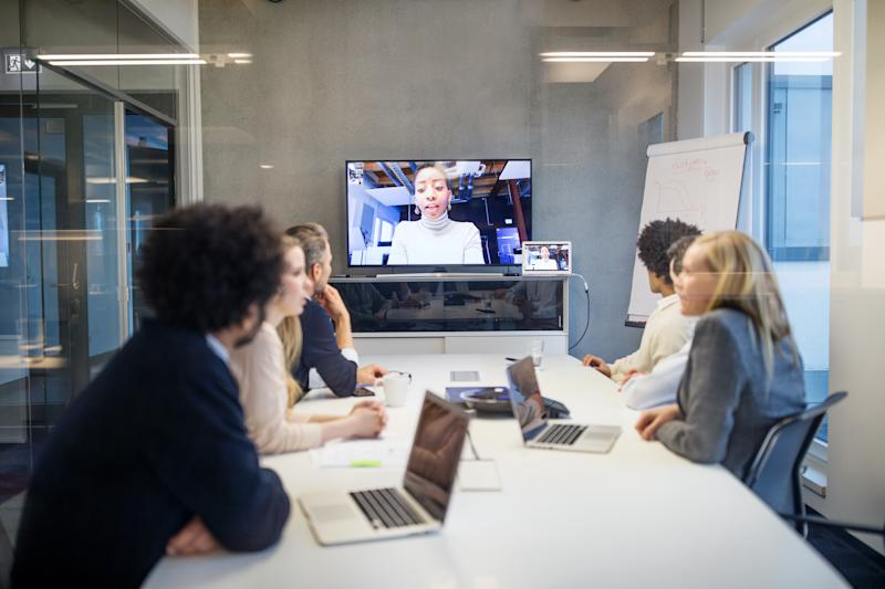 Group of business people having video conference in boardroom. Diverse business professionals having video conference meeting in office.