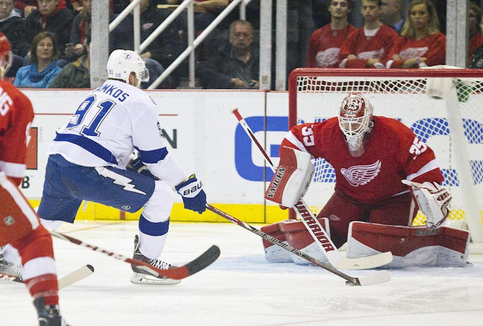 Tampa Bay Lightning forward Steven Stamkos (91) charges with the puck at Detroit Red Wings goalie Jimmy Howard (35) during the second period of an NHL hockey game in Detroit, Mich., Sunday, Nov. 9, 2014. (AP Photo/Tony Ding)