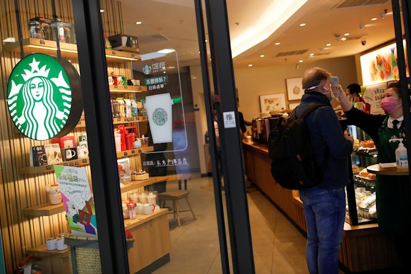 A worker uses a thermometer to check the temperature of a customer as he enters a Starbucks shop as the country is hit by an outbreak of the new coronavirus, in Beijing, China January 30, 2020. REUTERS/Carlos Garcia Rawlins