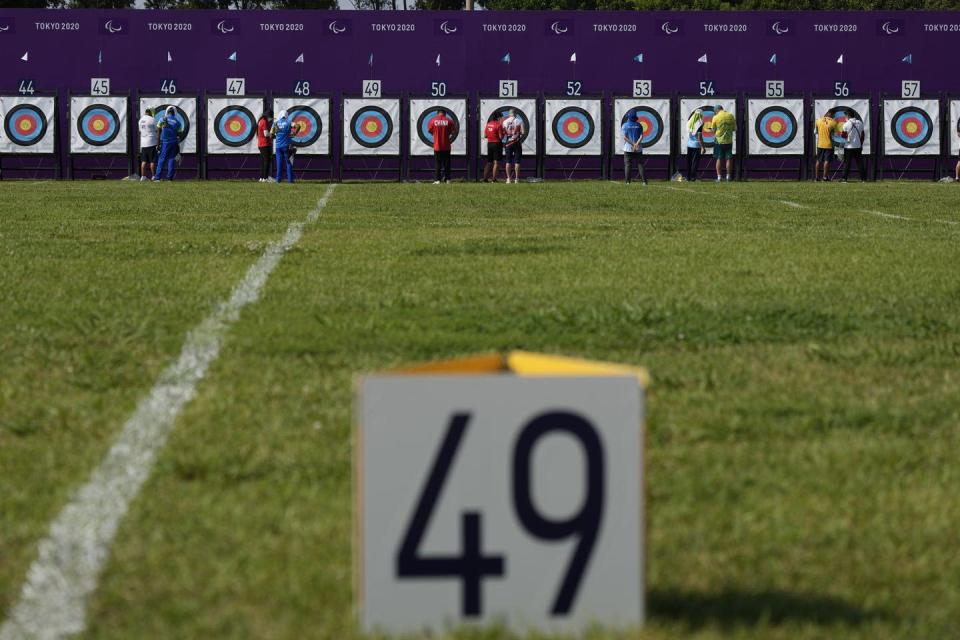 Athletes inspect their archery targets in the distance