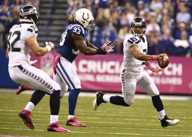 Seattle Seahawks quarterback Russell Wilson, right, throws to tight end Luke Willson, left, in front of Indianapolis Colts outside linebacker Erik Walden during the first half of an NFL football game in Indianapolis, Sunday, Oct. 6, 2013. (AP Photo/Brent R. Smith)