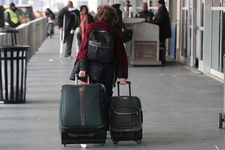 A woman carries her luggage to departing flights entrance at LaGuardia Airport in New York