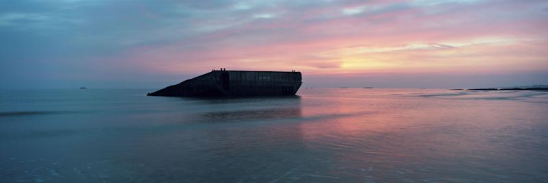 Sun rises over the remains of a section of the World War II Allied temporary Mulberry harbor built for the D-Day invasion, on what was known as Gold Beach, on May 01, 2019 in Arromanches, on the Normandy coast, France. (Photo: Dan Kitwood/Getty Images)