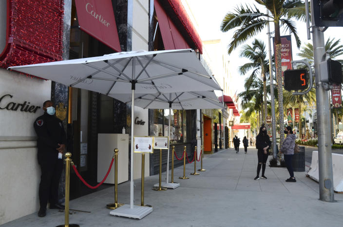 A security guard in a face mask stands outside Cartier jewelry shop with no customers on line during the coronavirus pandemic on Rodeo Drive, Thursday, Dec. 3, 2020, in Beverly Hills, Calif. The new stay-at-home order will last at least three weeks, cutting sharply into the most profitable shopping season and threatening financial ruin for businesses already struggling after 10 months of on-again, off-again restrictions and slow sales because of the pandemic. (AP Photo/Pamela Hassell)
