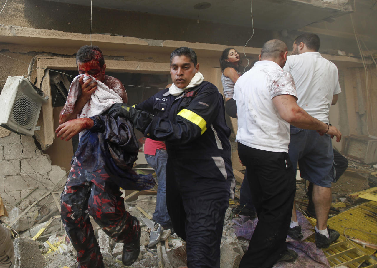 A Lebanese rescue worker, center, helps an injured man at the scene of an explosion in the mostly Christian neighborhood of Achrafiyeh, Beirut, Lebanon, Friday Oct. 19, 2012. A car bomb ripped through eastern Beirut on Friday, shearing the balconies off residential buildings and sending bloodied victims pouring out into the streets in the most serious blast this city has seen in years. (AP Photo/Hussein Malla)