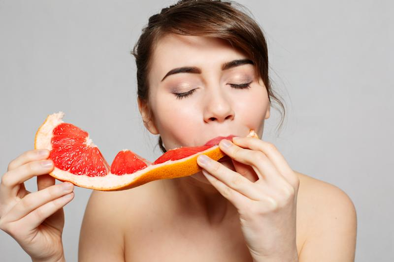 Young pretty woman or cute sexy girl with long hair holds grapefruit fruit slice,