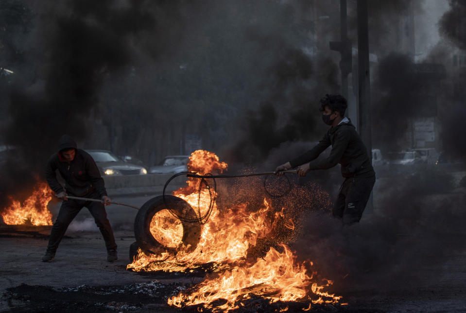 An anti-government protesters burns tires to block a road, during a protest in Beirut, Lebanon, Tuesday, March 2, 2021. Scattered protests broke out in different parts of Lebanon Tuesday after the Lebanese pound hit a record low against the dollar on the black market, a sign of the country's multiple crises deepening with no prospects for a new Cabinet in the near future. (AP Photo/Hassan Ammar)