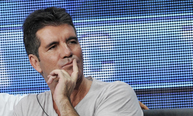 """Simon Cowell, a judge on the FOX series """"The X Factor,"""" looks on from the stage during a panel discussion on the show at the FOX 2013 Summer TCA press tour at the Beverly Hilton Hotel on Thursday, Aug. 1, 2013, in Beverly Hills, Calif. (Photo by Chris Pizzello/Invision/AP)"""