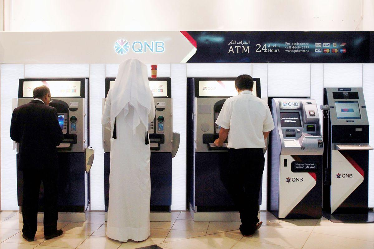 Customers operate automated teller machines (ATM) inside a Qatar National Bank SAQ (QNB) branch in Doha, Qatar, on Thursday, Nov. 22, 2012. Qatar Telecom QSC, the country's biggest company by revenue, is seeking a syndicated loan for about $1 billion to refinance existing debt, according to a person with direct knowledge of the deal.