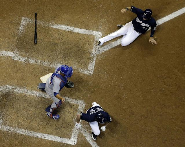 Milwaukee Brewers' Jeff Bianchi slides home to score on a suicide squeeze bunt by Logan Schafer (22), as Chicago Cubs catcher Welington Castillo stands by the plate during the ninth inning of a baseball game Tuesday, Sept. 17, 2013, in Milwaukee. The Brewers won 4-3. (AP Photo/Morry Gash)