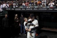 San Francisco Giants manager Bruce Bochy, right, smiles while holding his grandson in the dugout before a baseball game between the Giants and the Los Angeles Dodgers in San Francisco, Sunday, Sept. 29, 2019. (AP Photo/Jeff Chiu)
