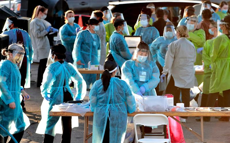 Medical personnel prepare to test hundreds of people lined up in vehicles in Phoenix, USA, organised by Equality Health Foundation, which focuses on care in underserved communities - AP