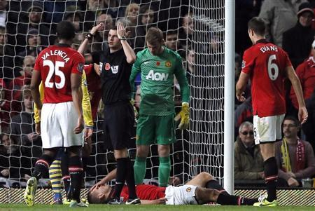 Referee Michael Oliver signals on the medics as Manchester United's Nemanja Vidic lays injured during their English Premier League soccer match against Arsenal at Old Trafford in Manchester, northern England, November 10, 2013. REUTERS/Phil Noble