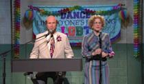"""<p><strong>For Ana Gasteyer's character:</strong> A printed dress with a curly wig and glasses.</p> <p><strong>For <a class=""""link rapid-noclick-resp"""" href=""""https://www.popsugar.com/Will-Ferrell"""" rel=""""nofollow noopener"""" target=""""_blank"""" data-ylk=""""slk:Will Ferrell"""">Will Ferrell</a>'s character:</strong> A tan suit with a printed tie and a fake beard.</p>"""