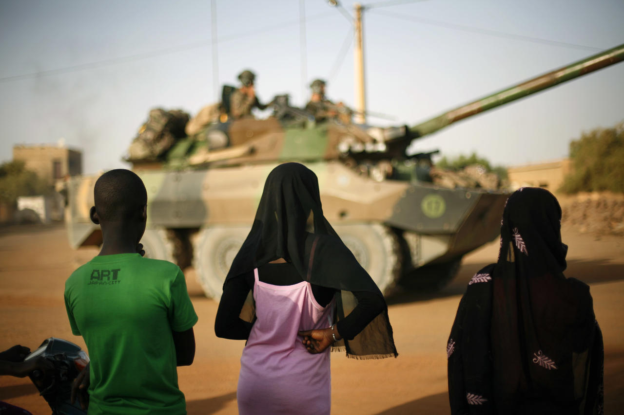 Malian teenagers watch a convoy of French military vehicles pass through Gao, northern Mali, Tuesday Feb. 19, 2013. A French soldier has been confirmed dead during a military operation in northern Mali, French President Francois Hollande said on Tuesday(AP Photo/Jerome Delay)