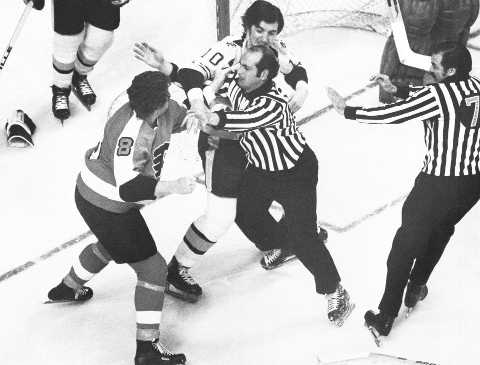 FILE - In this May 16, 1974, file photo, Philadelphia Flyers, Dave Schultz (8) left, tries to swing around linesman John D'Amico, center, to get to Boston Bruins Carol Vadnais in a first period fight during an NHL playoff game in Boston. Both players were penalized for fighting. In the 1970s, the Flyers had guys like Dave The Hammer Schultz, Bob The Hound Kelly and Andre Moose Dupont around to not just beat opponents but beat them up, too. More than 40 years later, the Flyers still carry the Bullies nickname but are hardly bullying anyone: Theyre one of only two teams in the NHL without a fight a quarter of the way through the season. (AP Photo/File)