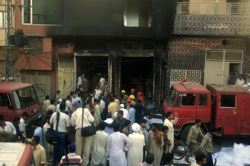 People stand outside a factory after a fire in Lahore, Pakistan on Tuesday, Sept 11, 2012. A fire that broke out in a factory in eastern Pakistan on Tuesday after sparks from a generator hit chemicals used to make shoes killed dozens of people, a Pakistani police officer said. (AP Photo/K.M. Chaudary)
