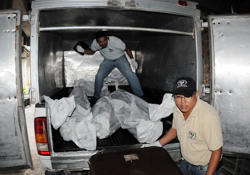 Forensic workers finish loading the bodies of three prisoners into a waiting vehicle, at the Hospital Escuela, in Tegucigalpa, Honduras, Saturday, Aug. 3, 2013.A riot at the country's main prison left at least three gang members dead and several guards injured. Police said members of the 18 gang clashed with common criminals in Honduras' National Penitentiary, located 10 miles (15 kilometers) north of the capital. Ambulances had taken three injured gang members from the prison to Hospital Escuela, where they died. (AP Photo/Fernando Antonio)