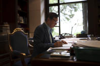In this Aug. 20, 2019, photo, Huawei's founder Ren Zhengfei reads documents in his office at the Huawei campus in Shenzhen in Southern China's Guangdong province. Ren says its troubles with President Donald Trump are hardly the biggest crisis he has faced while working his way from rural poverty to the helm of China's first global tech brand. (AP Photo/Ng Han Guan)
