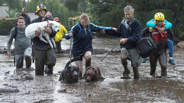 PHOTO: Emergency personnel evacuate local residents and their dogs after a mudslide in Montecito, Calif., Jan. 9, 2018. (Kenneth Song/Santa Barbara News-Press via Reuters)