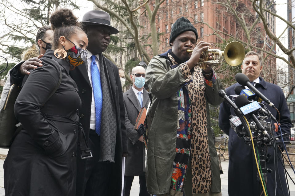 Katty Rodriguez, left, attorneys Ben Crump, second from left, and Paul Napoli, right listen to Keyon Harrold Sr. play his saxophone during a news conference to announce the filing of a lawsuit against Arlo Hotels and Miya Ponsetto, Wednesday, March 24, 2021, in New York. Keyon Harrold and his son were allegedly racially profiled in an Arlo hotel in Manhattan by Miya Ponsetto in December 2020. Ponsetto wrongly accused Keyon Harrold Jr. of stealing her phone and physically attacking him. (AP Photo/Mary Altaffer)