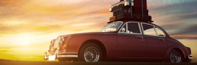 Retro red car with luggage on roof rack at sunset.