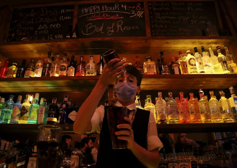 FILE PHOTO: A female bartender wearing a protective face mask mixes an alcoholic drink at a bar, in Beirut