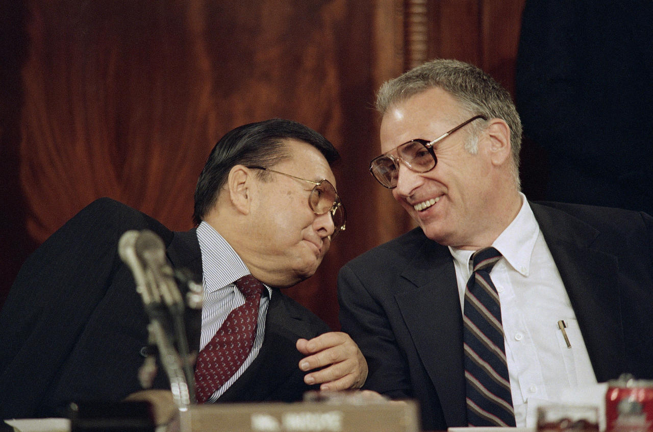 FILE - In this Friday, May 8, 1987 file photo, Sen. Daniel Inouye of Hawaii, left, and Rep. Lee Hamilton, of Indiana, who are the chairmen of the Senate and House select committees on the Iran-Contra affair, confer as the group continued hearings on Capitol Hill in Washington. Inouye, the influential Democrat who broke racial barriers on Capitol Hill and played key roles in congressional investigations of the Watergate and Iran-Contra scandals, died of respiratory complications, Monday, Dec. 17, 2012, according to his office. He was 88. (AP Photo/Lana Harris, File)
