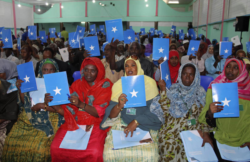 In this photo of Wednesday July 25, 2012, Somalia's constituency assembly members hold up copies of the proposed new constitution during the beginning of a nine-day meeting on Wednesday to examine, debate and vote on the proposed new constitution, in Mogadishu, Somalia.  Somali leaders are debating a new constitution that protects the right to abortion to save the life of the mother and bans the circumcision of girls. (AP Photo/Farah Abdi Warsameh)