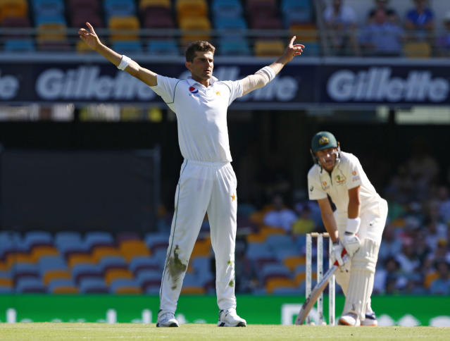 Pakistan's Shaheen Afridi, left, celebrates after getting the wicket of Australia's Tim Paine, right, during their cricket test match in Brisbane, Australia, Saturday, Nov. 23, 2019. (AP Photo/Tertius Pickard)