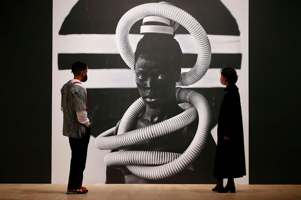 <p>Tate visitors pose in front of a self portrait photograph from an on-going series entitled 'Somnyama Ngonyama' by South African visual activist Zanele Muholi</p> (AFP via Getty Images)