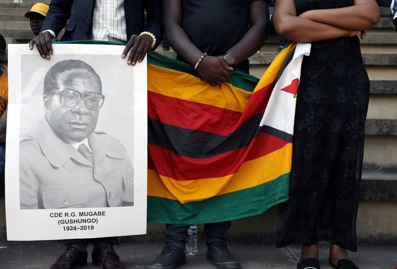 FILE PHOTO: Mourners hold a poster during the state funeral of Zimbabwe's longtime ruler Robert Mugabe at a national sports stadium in Harare