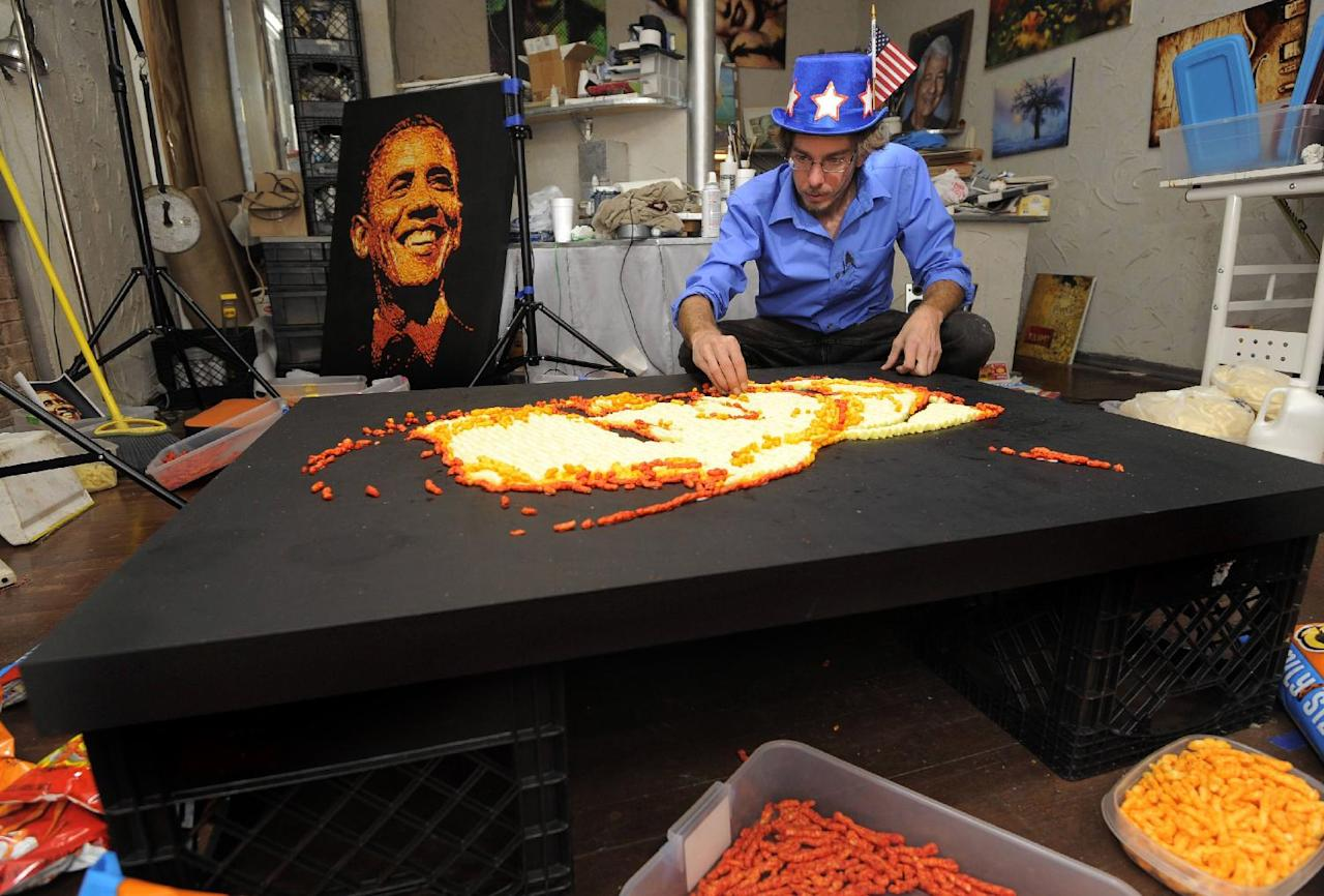 IMAGE DISTRIBUTED FOR CHEETOS - Artist Jason Baalman puts the finishing touches on a Cheetos portrait of former Gov. Mitt Romney Tuesday, Oct. 2, 2012, in Baalman's Colorado Springs, Colo., studio. Today, the Cheetos brand unveiled a new electoral polling model with the unveiling of 3 feet by 4 feet one-of-a-kind Cheetos portraits of the Democratic and Republican presidential nominees – President Barack Obama and former Gov. Mitt Romney. Debuting on Facebook today at 11 a.m. CT, fans are encouraged to vote for their candidate's portrait – made entirely of more than 2,000 individual Cheetos cheese snacks – for a chance to win the actual portrait. (Photo by Jack Dempsey/Invision for Cheetos/AP Images)