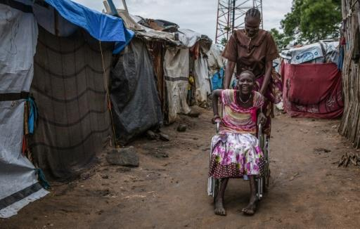 A mother's love: Eleven-year-old Nyamet Steven was born with cerebral palsy -- her mother Nyayom Steven, who has six other children, pushes her wheelchair through the camp