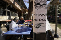 A sign requiring make is seen near diners eating at a restaurant on the River Walk, Wednesday, March 3, 2021, in San Antonio. Gov. Greg Abbott says Texas is lifting a mask mandate and lifting business capacity limits next week. (AP Photo/Eric Gay)