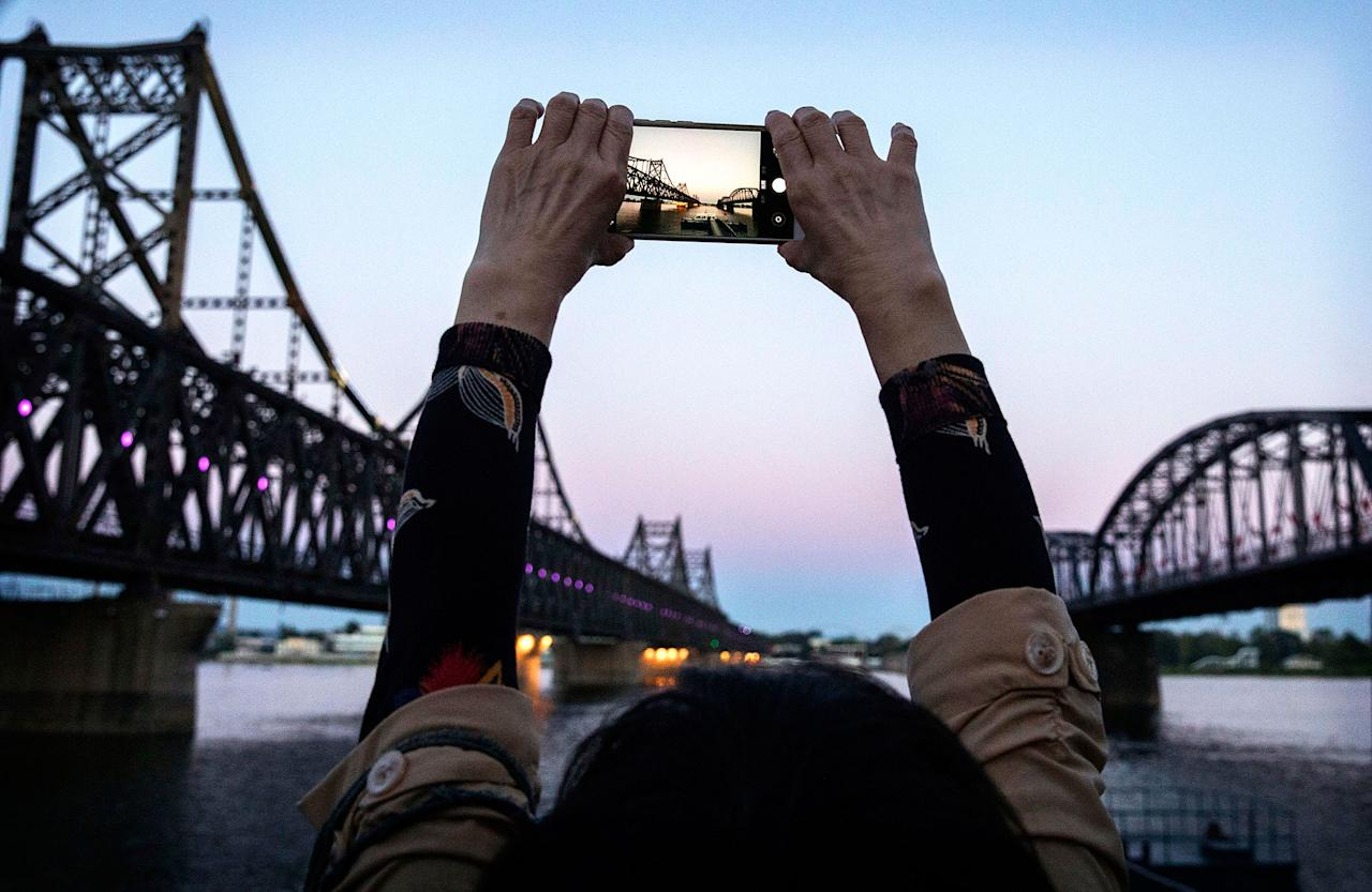 """<p>A Chinese tourist takes pictures between """"Friendship Bridge"""", left, and """"Broken Bridge"""", right, as she looks across the Yalu river from the border city of Dandong, Liaoning province, northern China towards the city of Sinuiju, North Korea on May 23, 2017 in Dandong, China. (Photo: Kevin Frayer/Getty Images) </p>"""