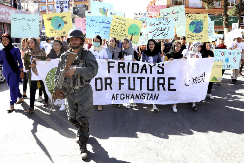 Young people attend a Climate Strike rally, as Afghan security forces guard them in Kabul, Afghanistan, Friday, Sept. 20, 2019.  In the Afghan capital,  where people are dying every day in horrific bomb attacks, a young generation, worried that if war doesn't kill them climate change will, took part in the global climate strike. (AP Photo/Ebrahim Noroozi)