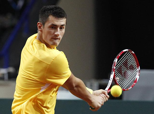 Australia's Bernard Tomic returns a shot to Poland's Lukasz Kubot during their Davis Cup play-off round tennis match in Warsaw, Poland, Sunday, Sept. 15, 2013.(AP Photo/Czarek Sokolowski)