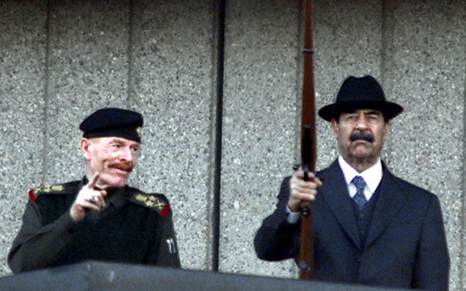 Al-Douri at a military parade in Baghdad with Saddam Hussein in 2000 - Karim Sahib/AFP via Getty Images