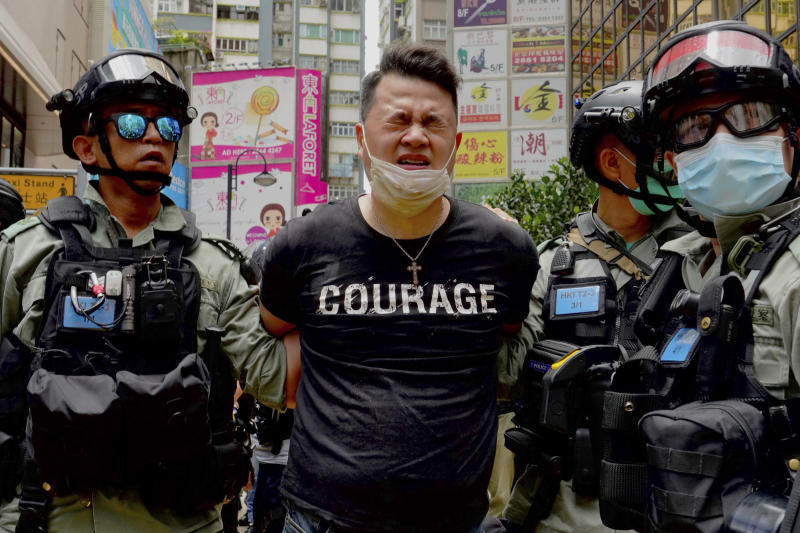 Police detain a protester after bering sprayed with pepper spray during a protest in Causeway Bay before the annual handover march in Hong Kong, Wednesday, July 1, 2020. Hong Kong marked the 23rd anniversary of its handover to China in 1997, and just one day after China enacted a national security law that cracks down on protests in the territory. (AP Photo/Vincent Yu)