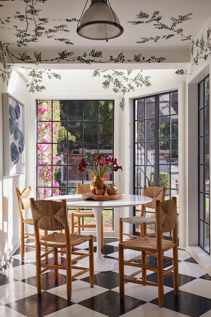 "<div class=""caption""> In the breakfast nook, a fresh coat of paint transformed the wood floors into a black-and-white optical illusion, and the Valle hand-painted vines create a secret-garden feel. An Eero Saarinen table surrounded by Charlotte Perriand chairs completes the scene, while a Lucien Smith piece hangs nearby. </div>"