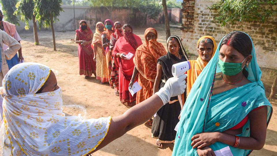 Voters undergo thermal screening as they stand in a queue outside a polling station to cast their votes for the first phase of Bihar Assembly Elections, at Naubatpur in Patna, Wednesday, 28 October.