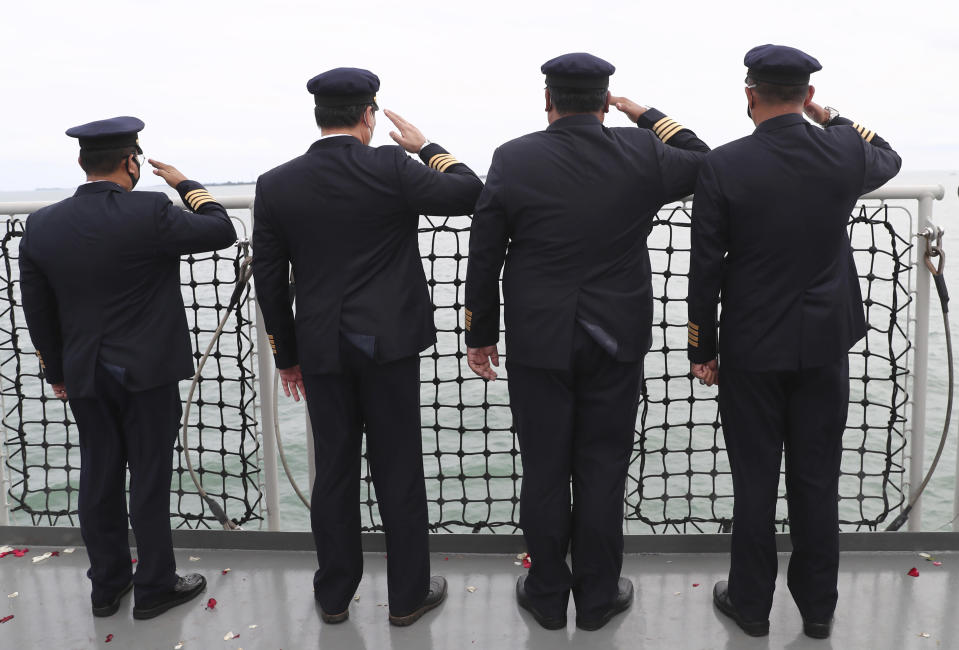 Indonesian pilots salute during a memorial ceremony for the victims of Sriwijaya Air flight SJ-182 on the deck of Indonesian Navy Ship KRI Semarang that sails in the Java Sea where the plane crashed on Jan. 9 killing all of its passengers, near Jakarta in Indonesia, Friday, Jan. 22, 2021. (AP Photo/Tatan Syuflana)