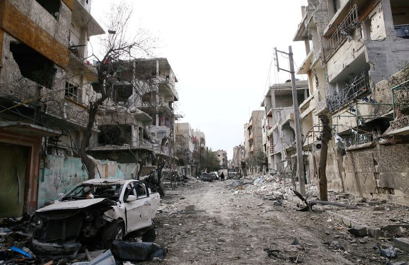 FILE PHOTO: Damaged cars and buildings are seen in the besieged town of Douma, Eastern Ghouta, Damascus